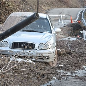 A car is stuck in the mud from a landslide Sunday, Feb. 18, 2018, on Gershon St. between Luella St. and Sunset Ave. in Spring Hill. The hillside is falling onto the street, and the street is collapsing over the hill side below.