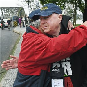 Former U. S. Marine George Haught of Monaca is comforted by good friend and fellow Marine Danny Cholewa of Benton Harbor, Mich. on Feb. 1 after crossing what is now the Truong TIen Bridge in Hue City, Vietnam. In 1968, both men along with other members of Golf Company, 2nd Battalion 5th Marines, fought their way across a previous bridge during the Battle of Hue. Mr. Haught was awarded three Purple Hearts for his service in Vietnam.