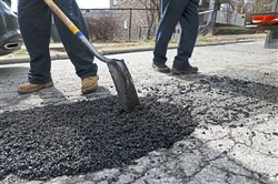Workers cold patch a pothole on Brookline Boulevard in Brookline in February.