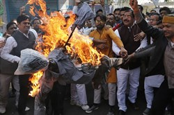 India's opposition Congress party supporters shout slogans as they burn an effigy as they protest against the alleged $1.8 billion bank fraud in Lucknow, India, on Feb. 20, 2018.