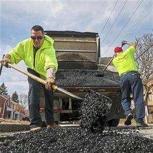 City workers on Feb. 20, 2018 employing a temporary fix on potholes around town. With all of the rain expected through the weekend, officials warn that a more permanent fix will be stalled.