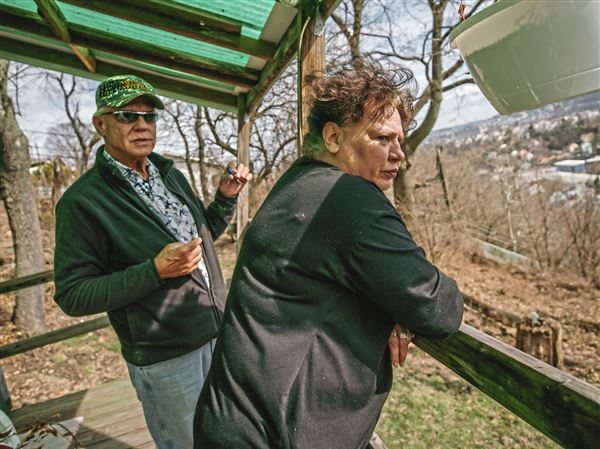 "James and Helen Jackson stand on the back porch of their home Tuesday on Kenzig Avenue in Spring Hill. They were told to evacuate their home because the city has deemed it ""imminently dangerous."""