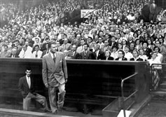 Billy Graham emerges from the Pirates' dugout at Forbes Field to deliver a sermon in September 1952.