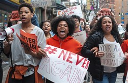 Pittsburgh CAPA High School students Mia Arrington, center, 18, of West End, and Cheyenne Springette, right, 17, of Mt. Oliver, lead chants as they march down Liberty Avenue during a walk-out in solidarity with other high schools across the country on Wednesday after a mass shooting at a Parkland, Fla. school last week.