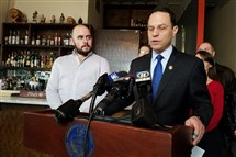 Pennsylvania Attorney General Josh Shapiro addresses reporters while standing alongside Kevin Cox, a co-owner of Bar Marco, at the Strip District bar on Thursday. Mr. Shapiro said he strongly opposes the U.S. Department of Labor's proposed changes in tip pooling, which would reverse a 2011 law preventing employers from collecting and distributing tips to anyone other than tipped employees.