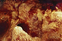 This color-enhanced image provided by Hipolito Collado Giraldo in February 2018 shows three hand stencils in the Maltravieso Cave in Cáceres, Spain. One has been dated to at least 66,000 years ago.