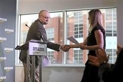 Bill Kaper, general manager of Amazon's Pittsburgh office, shakes hands with Melissa Horvath as she takes the podium to speak during a press conference at the company's South Side offices on Thursday. Ms. Horvath, the owner of Sewickley-based Sweet Water Decor, said Amazon has helped her grow her business.
