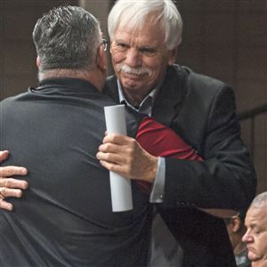 "John Giammarco, left, 52, of McKees Rocks, gives a hug to Mike Zmijanac after speaking in support of Zmijanac at Wednesday's Aliquippa school board meeting. ""He's a great coach, he's a better person,"" Giammarco said of Zmijanac."