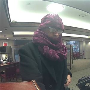 A surveillance photo of the man who robbed Key Bank on Thursday morning at 300 Sixth Ave. in Downtown Pittsburgh. The robber did not display a weapon but had an unusual outfit. He carried a green and white umbrella and a neon yellow tote bag.