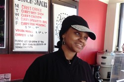 "Lydiah Wanyoike smiles while chatting to a customer in her tiny take-out restaurant on Grant Street, Downtown. Ms Wanyoike is closing in two weeks, but hope to relocate somewhere else in Downtown. If not, she hopes to ""go anywhere there is diversity."""