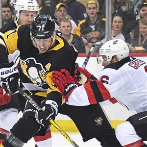 New Jersey's Andy Greene knocks Evgeni Malkin off the puck during a Feb. 27 game.
