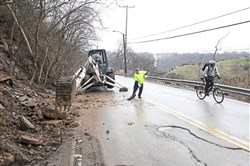A cyclist rides past as workers remove mud, concrete and other debris in March  after a landslide fell along Forward Avenue near Commercial Street between Squirrel Hill and Swisshelm Park.