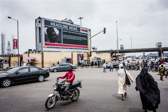 In this file photo, a giant electronic advertising screen displays news about Muhammadu Buhari, Nigeria's president, to pedestrians in Lagos, Nigeria, on July 26, 2017.