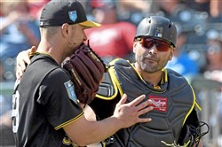 Pirates catcher Francisco Cervelli talks with pitcher Chad Kuhl after the first inning against the Braves at Champion Stadium on March 5, 2018.