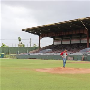 A worker stands on the baseball mound at Parque Yldefonso Sol‡ Morales, the baseball stadium in Caguas, Puerto Rico, on Monday, Jan. 29, 2018. The ballpark cannot be used right now due to Hurricane Maria's destruction, and the team, Criollos de Caguas, had to play elsewhere.