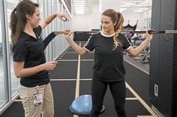 Larissa Symington, UPMC Sports Medicine athletic trainer, and Madison Brunner, UPMC employee, prepare to demonstrate a double and single leg squat, using a hockey stick to keep proper posture during the exercise at UPMC Lemieux Sports Complex in Cranberry.