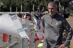 Jeff Foster examines signs and mementos left on the makeshift memorial in front of Marjery Stoneman Douglas High School on March 8, 2018, in Parkland, Fla.