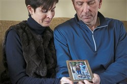 Christine Henney holds back tears as she and her husband Ray hold a photo of their son R.J. Henney, who they lost to an opioid overdose, and his sister Megan Henney Friday at their home in Mt. Lebanon.