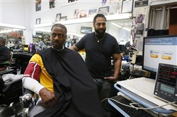 In this March 11, 2018, photo, barber Eric Muhammad, owner of A New You Barbershop, measures the blood pressure of customer Marc M. Sims in Inglewood, Calif.