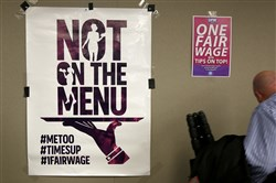 In this Feb. 20, 2018, photo, signs supporting fair wages and treatment are displayed at a discussion about subminimum wage workers that depend on tips for their living in New York.