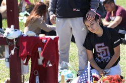 Gabriel Constantino and Nikki Healey (R) from Marjory Stoneman Douglas High School stand together at a memorial after walking out of school to honor the memories of 17 classmates and teachers that were killed during a mass shooting at the school March 14, 2018, in Parkland, Florida.