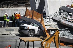 Members of the National Transportation Safety Board on March 16, 2018, in Miami investigate the scene where a pedestrian bridge collapsed a few days after it was built near Florida International University.