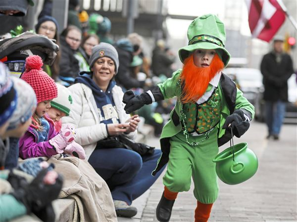 Brady Kuntz, 6, sprints down the street to the next parade goer to hand out candy in a leprechaun costume during the 2018 Pittsburgh St. Patrick's Day Parade Saturday, Downtown.