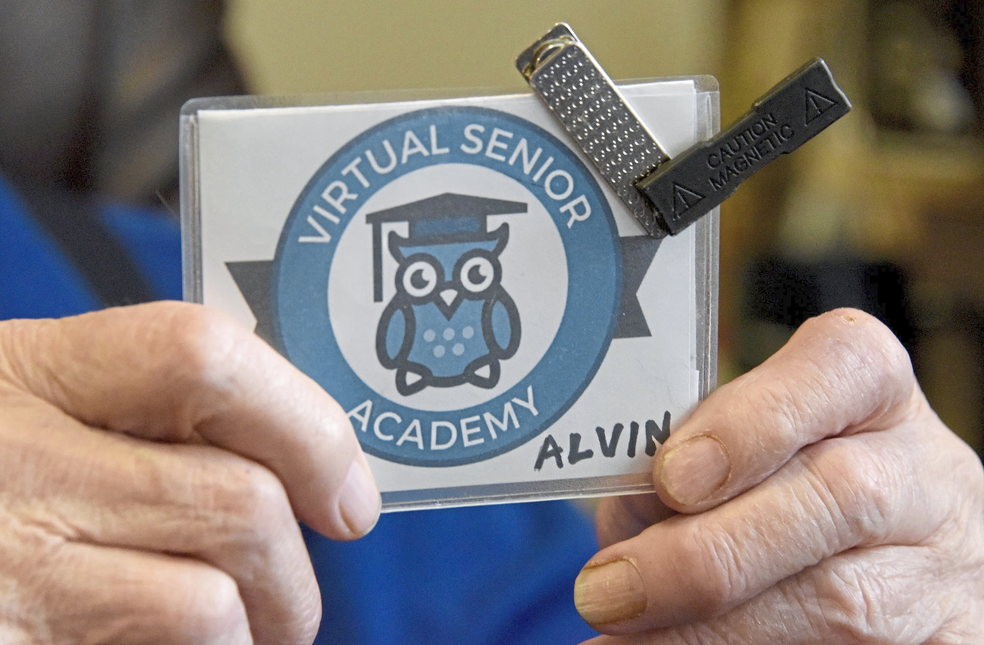 20180316dsSENIORACADEMY0319Local07-6 Al Fineman, 97, holds his Virtual Senior Academy logo, at his home at Riverview Towers apartments in Squirrel Hill. He is part of the Jewish Healthcare Foundation-sponsored Virtual Senior Academy, using their home computers to take various online classes and interact with each other through the video conferencing.