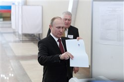 Russian President Vladimir Putin, front, votes at a polling station in Moscow on March 18, 2018.