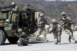 In this March 25, 2015, file photo, U.S. Army soldiers from the 25th Infantry Division's 2nd Stryker Brigade Combat Team and South Korean soldiers take their position during a demonstration of the combined arms live-fire exercise as a part of the annual joint military exercise Foal Eagle between South Korea and the United States at the Rodriquez Multi-Purpose Range Complex in Pocheon, north of Seoul, South Korea.