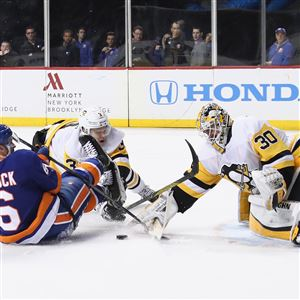 Penguins Olli Maatta takes a penalty for holding Islanders Ryan Pulock during the second period at the Barclays Center on Tuesday.