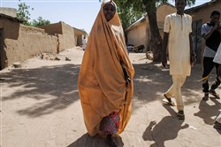 A girl released by Boko Haram walks with her father in Dapchi on March 21, 2018.