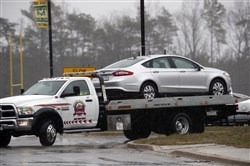 A car is towed away on a flatbed tow-truck away from the parking lot of Great Mills High School, the scene of a shooting, Tuesday, March 20.