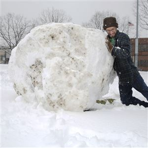 Matt Kory of Homestead takes a break from working as a software engineer at Google in Bakery Square to build a huge snowball Wednesday in Mellon Park.