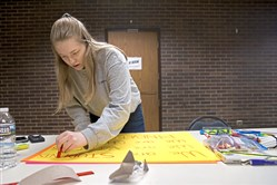 Holly Vetter, 15, of East Pittsburgh, works on a poster with her friends. Seventeen students from Woodland Hills High School are traveling to Washington, D.C. for the March for Our Lives on Saturday.
