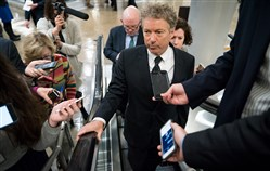 Sen. Rand Paul, R-Ky., heads to a vote on Capitol Hill in Washington Wednesday. With government funding set to run out this weekend, congressional leaders neared agreement Wednesday on a voluminous spending bill.