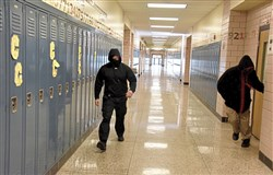 Security officers posing as mock intruders rush down a hallway inside Pittsburgh Carrick High School trying to find unlocked classroom doors during an active-shooter training session Friday morning.