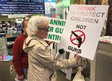 Tina Hobson, 88, checks a sign as she picks up a batch at a print shop in Washington, D.C. Hobson and others are going to the March for Our Lives on Saturday to support the cause and hand out cookies.