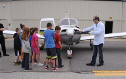 In this June 2013 file photo, Jonathan Plesset, right, shows students the plane at Allegheny County Airport that he and Brad Childs, far left, use when they rescue animals from shelters as part of the Pittsburgh Aviation Animal Rescue Team (PAART).