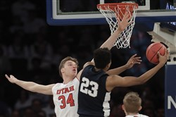 Penn State guard Josh Reaves (23) shoots next to Utah forward Jayce Johnson (34) in the first quarter of an NCAA college basketball game for the NIT championship Thursday, March 29.
