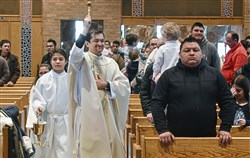 The Rev. Fernando Torres bless the Mass Sunday, April 1, 2018, at St. Catherine of Siena Catholic Church in Beechview. More than 400 area residents attended the Spanish-language Easter Mass.