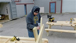 Tony Lang from Millvale puts together one of 26 picnic tables to be used for the Pittsburgh Food Truck Park along Millvale's Riverfront Park.