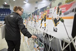 Kathleen Keen, who works with the Humboldt Broncos, arranges photos of Broncos players for a vigil at the Elgar Petersen Arena in Humboldt, Saskatchewan on Sunday.