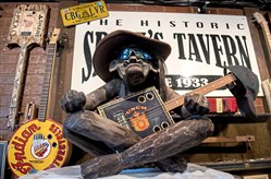 The mascot Blu Magoo sits on top of an amp with a guitar at 50 Cigar Box Guitars Museum in New Alexandria.