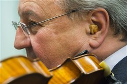 Charles Stegeman, 63, violinist and concertmaster of both the Pittsburgh Opera Orchestra as well as the Pittsburgh Ballet Orchestra Professor practices while wearing special earplugs on Friday, April 13, 2018. (Lake Fong/Post-Gazette)