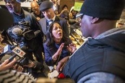 Camille Hymes, center, regional vice president of Mid-Atlantic operations at Starbucks Coffee Company, speaks with Asa Khalif, of Black Lives Matter, right, after protesters entered the coffee shop, Sunday, April 15, 2018, demanding the firing of the manager who called police resulting in the arrest of two black men on Thursday. The arrests were captured on video that quickly gained traction on social media. (Mark Bryant/The Philadelphia Inquirer via AP)