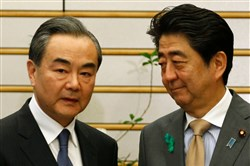 Japan's Prime Minister Shinzo Abe, right, looks at China's Foreign Minister Wang Yi at the start of their meeting at Mr. Abe's official residence in Tokyo on April 16, 2018.