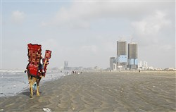 Tourists take a camel ride along a mostly empty stretch of Clifton Beach in Karachi, Pakistan on March 19, 2018. The beach is maintained by Pakistan's Defence Housing Authority.