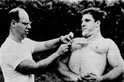 "A photo of Bruno Sammartino in a 1958 edition of the Pittsburgh Press. The caption reads: ""Sanford Kapner, a noted weight lifter, assists Bruno in developing his powerful body. The young giant's chest measures whopping 58 inches."""