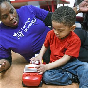 Lesely (cq) Crawford, owner of the ABK Learning & Development Center in the Hill District, explains the workings of a fire truck to Brandon Green, 3, on Tuesday.